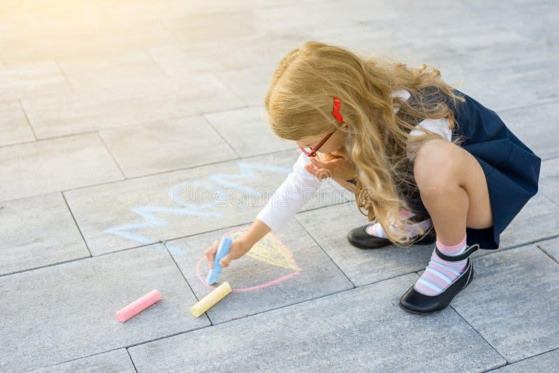 Sohn gibt der Mama eine Blume Kindermädchen zeichnet Geschenküberraschung zur Mama - Bild von Zeichenstiften auf dem Asphalt lizenzfreie stockfotos