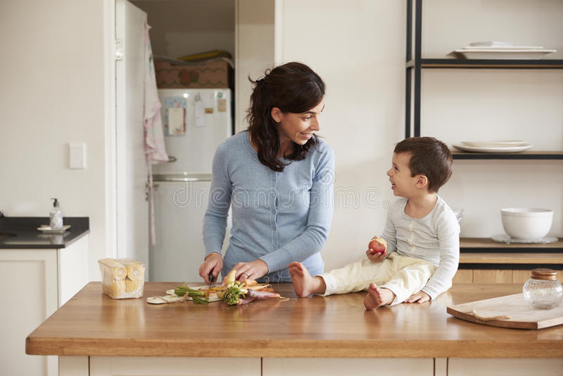 Sohn-helfende Mutter, zum des Lebensmittels auf Küchen-Insel zuzubereiten lizenzfreie stockfotos