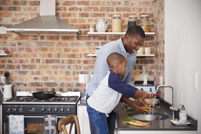 Sohn-helfender Vater To Prepare Vegetables für Mahlzeit in der Küche lizenzfreie stockfotografie