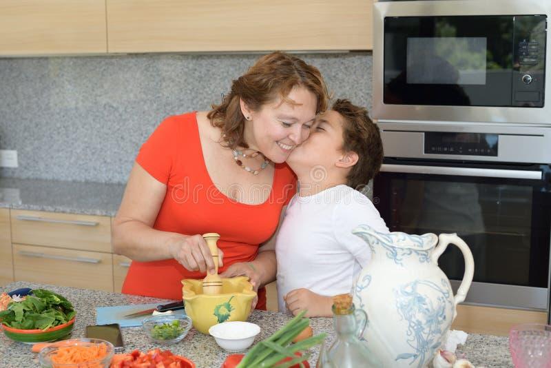 Sohn küsst seine Mutter, während sie das Mittagessen vorbereiten stockfoto