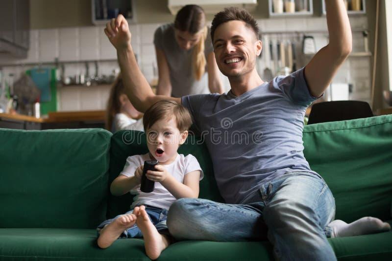 Sohn mit aufpassendem Fußball des Vaters im Fernsehen zusammen stockbild