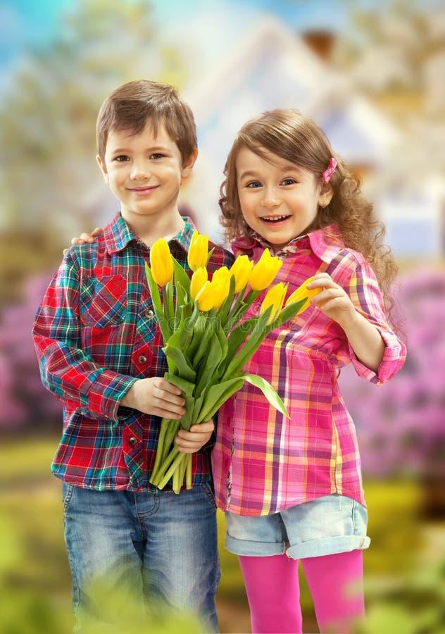 Sohn mit dem Blumenstrauß, der Überraschung für Mutter vorbereitet stockbilder