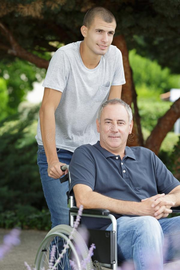 Sohn und Vati, die in Rollstuhl oudtoors sitzen stockfoto
