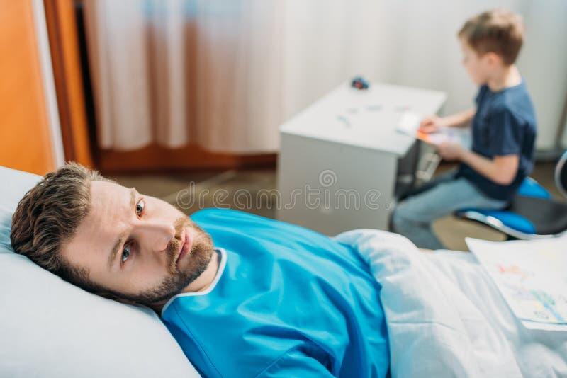 Sohnzeichnungsbilder während kranker Vater, der auf Krankenhausbett am Bezirk legt lizenzfreie stockbilder