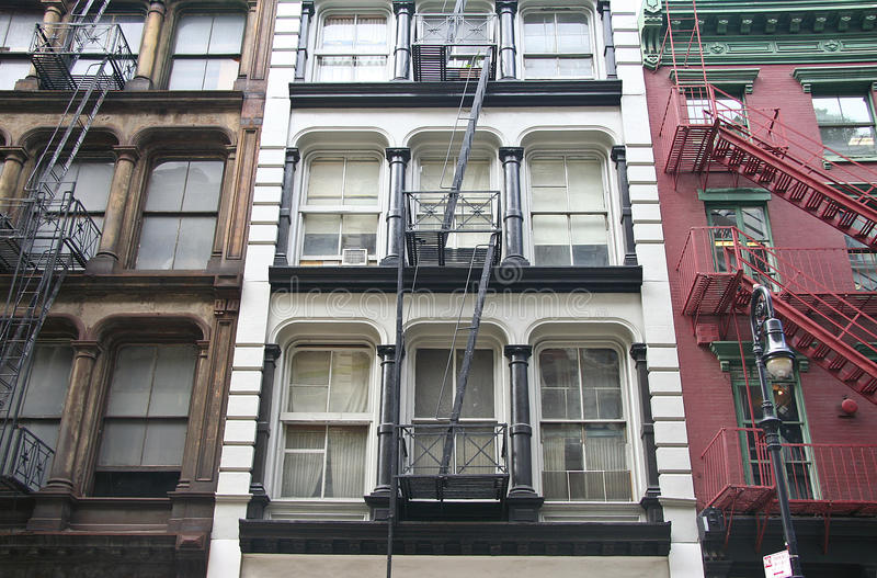 Soho fire escape. Three colorful, red, brown and white, apartment buildings facades with emergency escapes. Typical New York City rental complexes with fire stock photos