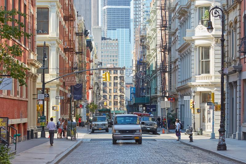 Soho street with cast iron buildings and people in New York. NEW YORK - SEPTEMBER 14: Soho street with cast iron buildings and people in a sunny day on September stock photos