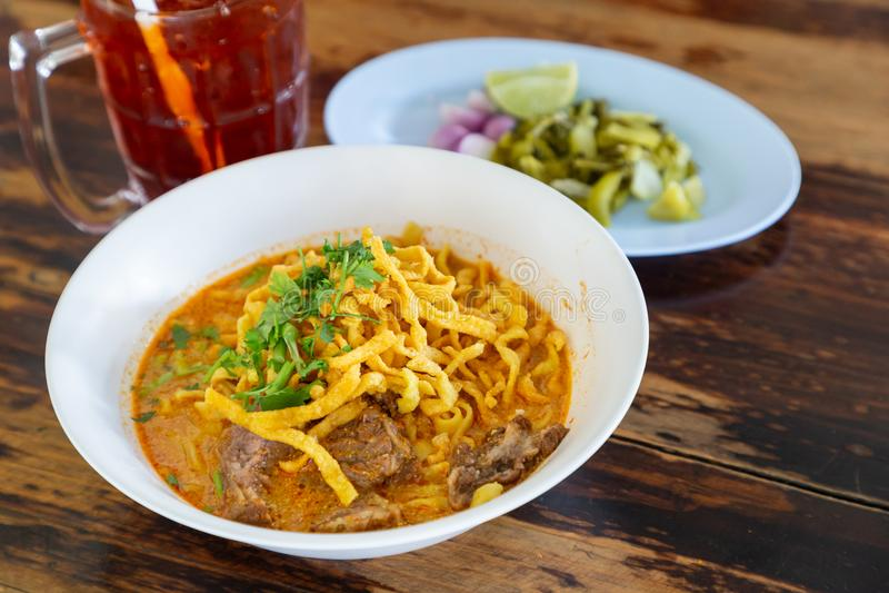 Soi surrado de Khao da sopa de macarronete com carne e leite de coco picante na tabela de madeira fotografia de stock
