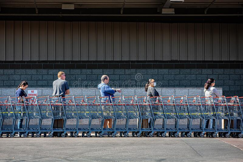Soical distancing in a line outside wholesale warehouse during the coronavirus pandemic royalty free stock images