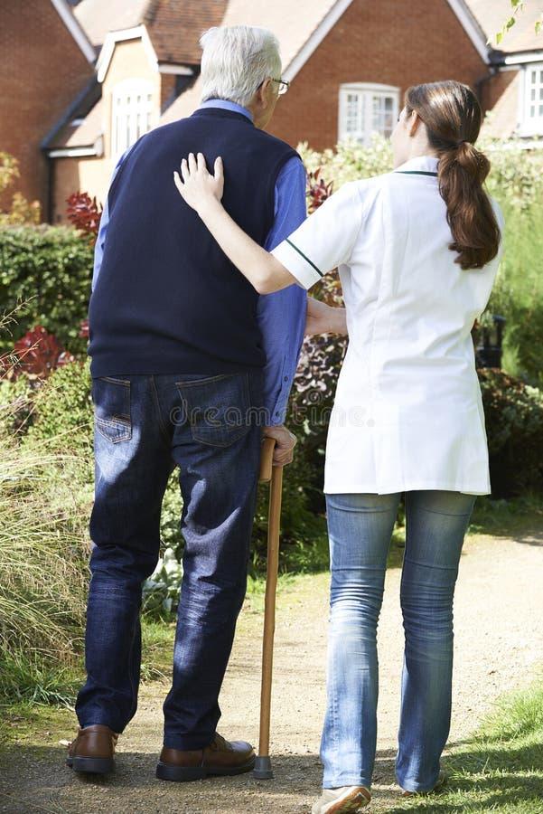 Soignant aidant l'homme supérieur à marcher dans le jardin utilisant le bâton de marche image stock