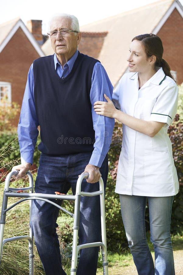 Soignant aidant l'homme supérieur à marcher dans le jardin utilisant le cadre de marche photographie stock libre de droits