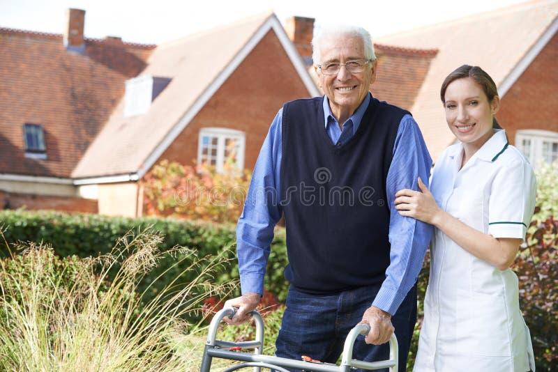 Soignant aidant l'homme supérieur à marcher dans le jardin utilisant le cadre de marche image libre de droits