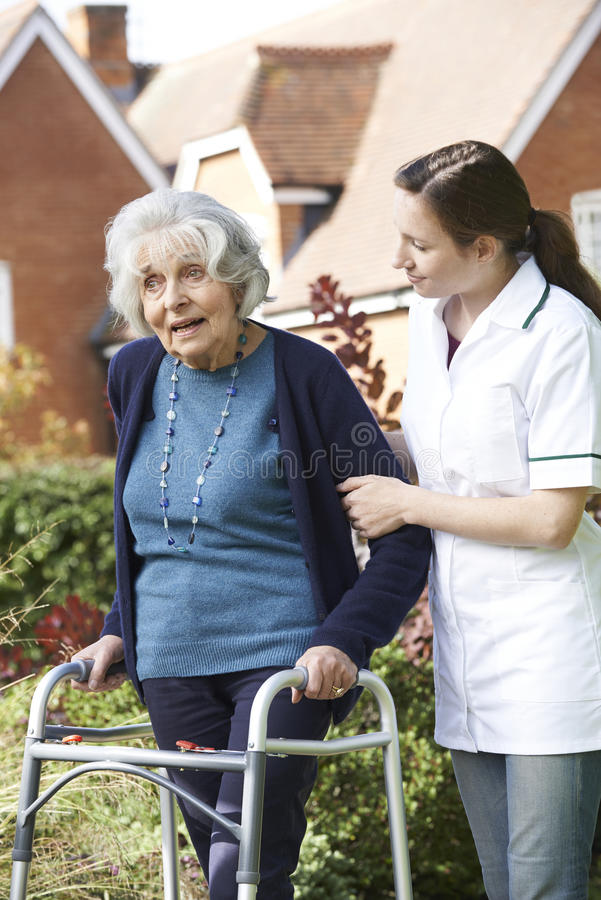 Soignant aidant la femme supérieure à marcher dans le jardin utilisant le cadre de marche photo stock