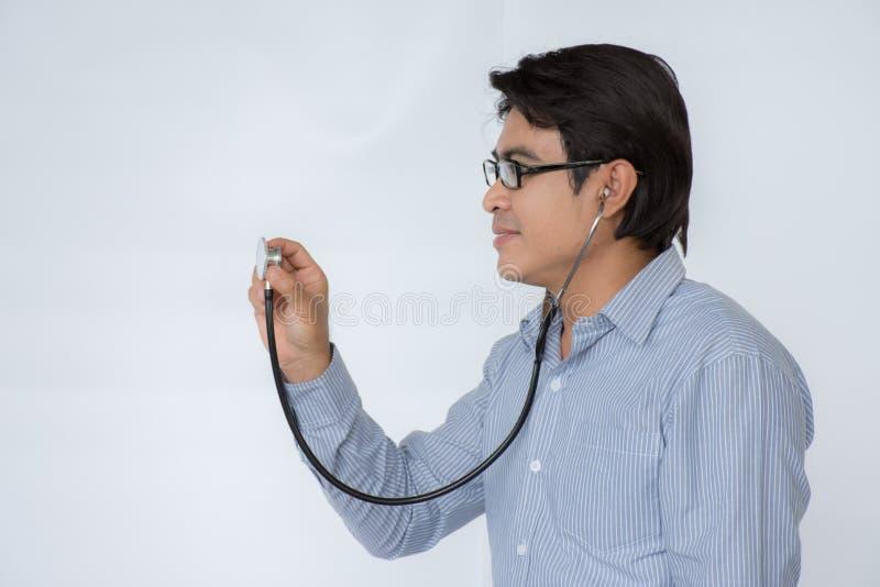 Soignez écouter un battement de coeur avec un stéthoscope au-dessus du fond blanc photos libres de droits