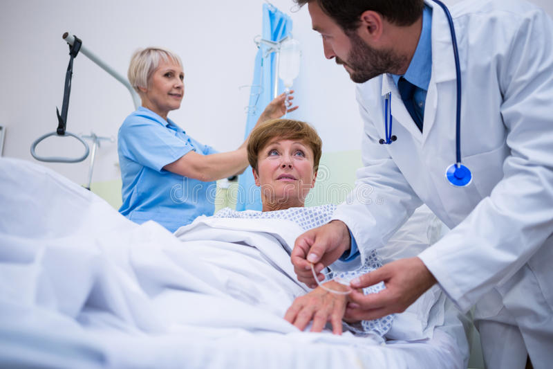 Soignez attacher l'égouttement d'iv sur la main patiente de s images stock