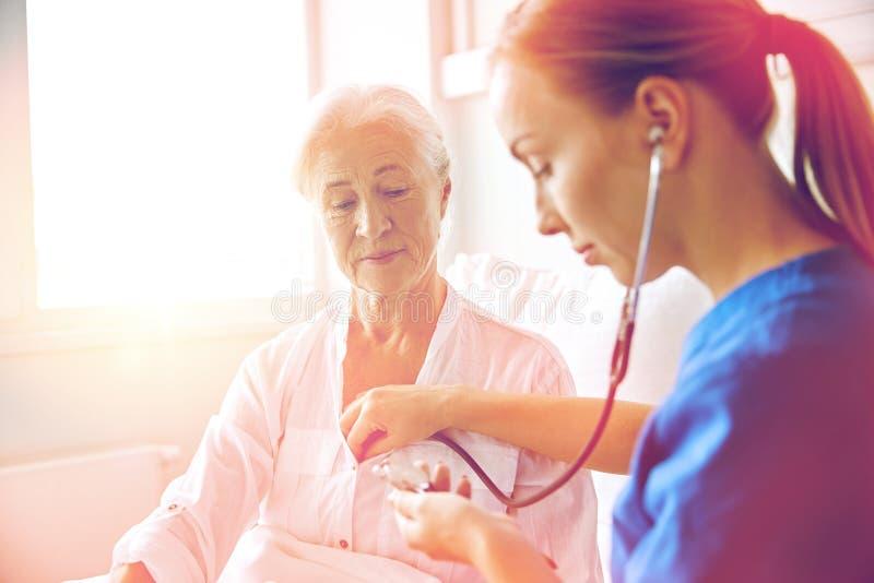 Soignez avec le stéthoscope et la femme supérieure à la clinique photos stock