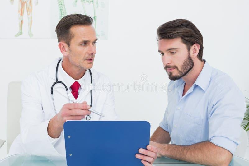 Soignez discuter des rapports avec le patient au bureau médical images stock