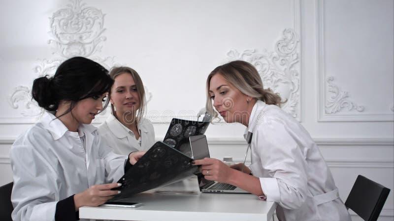 Soignez et deux étudiantes studing avec la photo de rayon X image libre de droits