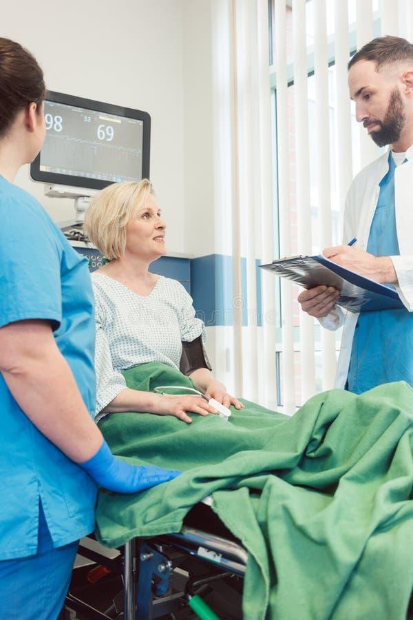 Soignez et soignez parler au patient dans la chambre de rétablissement de l'hôpital photographie stock