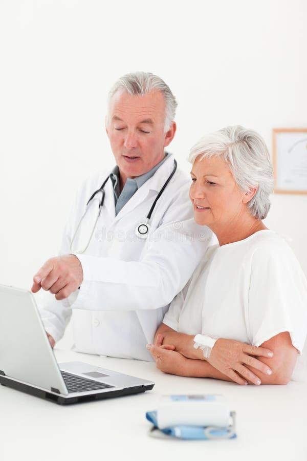 Soignez et son patient regardant l'ordinateur portatif images stock