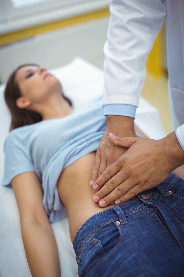 Soignez examiner l'estomac d'un patient féminin photo stock