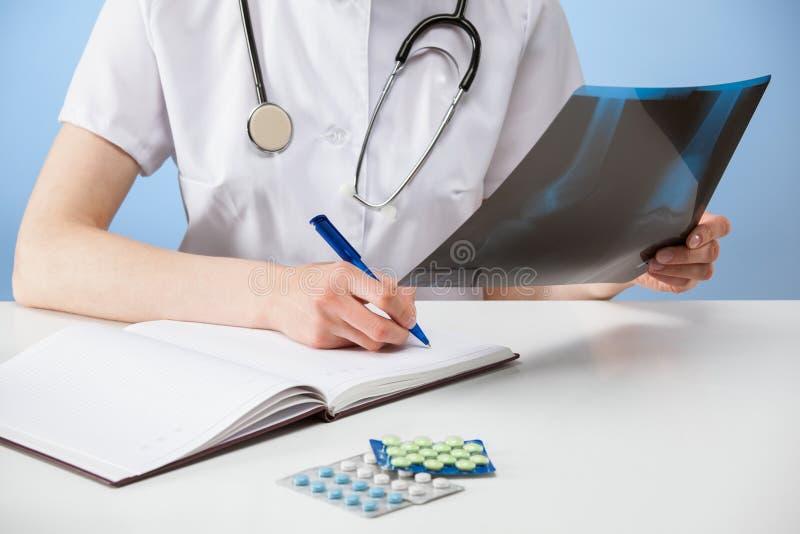Soignez examiner une photographie de rayon X et faire des notes image stock