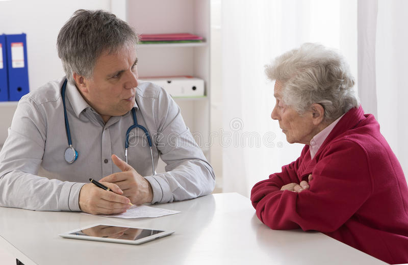 Soignez expliquer le diagnostic à son patient féminin supérieur images stock