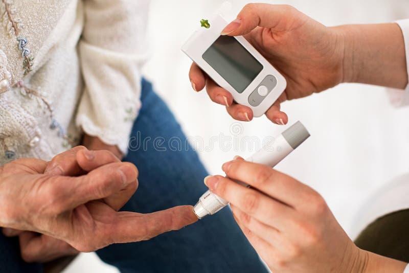Soignez faire l'analyse de sang de diabète sur la femme supérieure, plan rapproché images stock