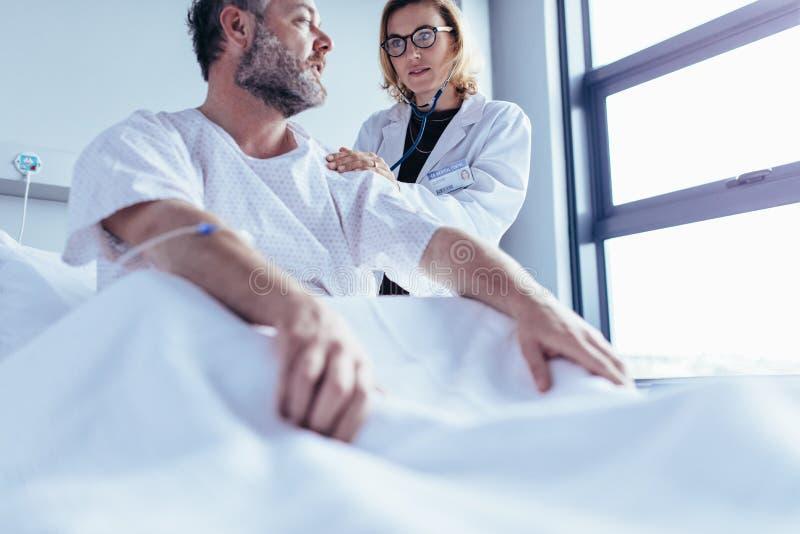 Soignez faire le contrôle de santé de l'homme hospitalisé photo libre de droits