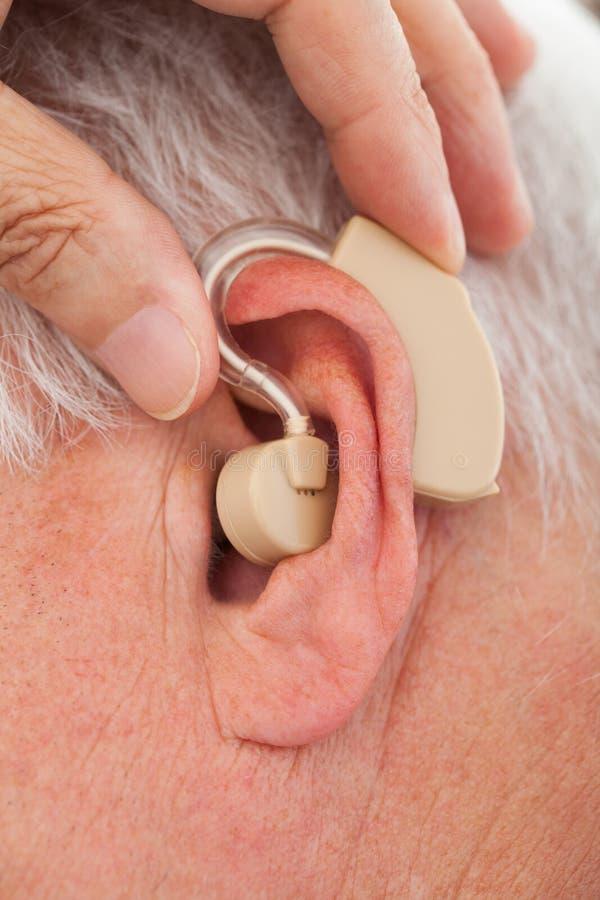 Soignez insérer la prothèse auditive dans l'oreille d'homme supérieur image libre de droits