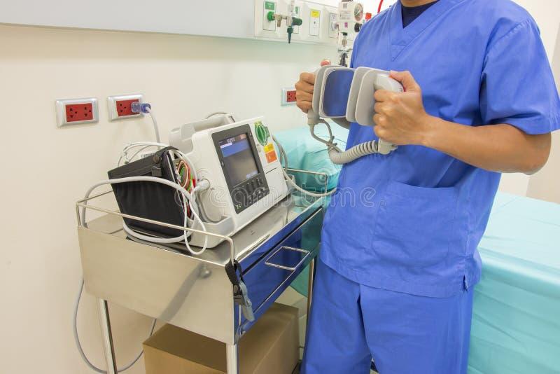 Soignez l'électrocardiogramme d'utilisation ou l'ECG et examinez le défibrillateur photographie stock libre de droits