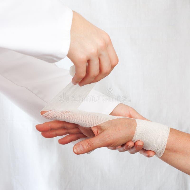 Soignez la couverture la main du patient par le bandage images stock