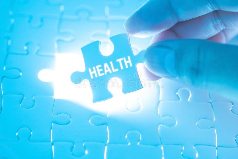 Soignez la main tenant un puzzle denteux avec le mot de santé Concept il images stock