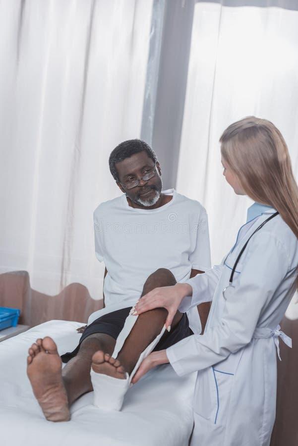 Soignez la mise sur la fonte de plâtre sur la jambe blessée de patient d'afro-américain photographie stock libre de droits
