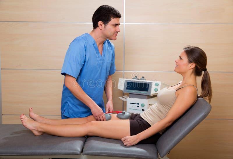 Soignez le thérapeute vérifiant l'electrostimulation de muscle à la femme image stock