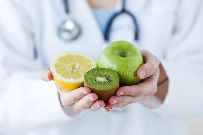 Soignez les mains tenant le fruit tel que la pomme, le kiwi et le citron photo libre de droits