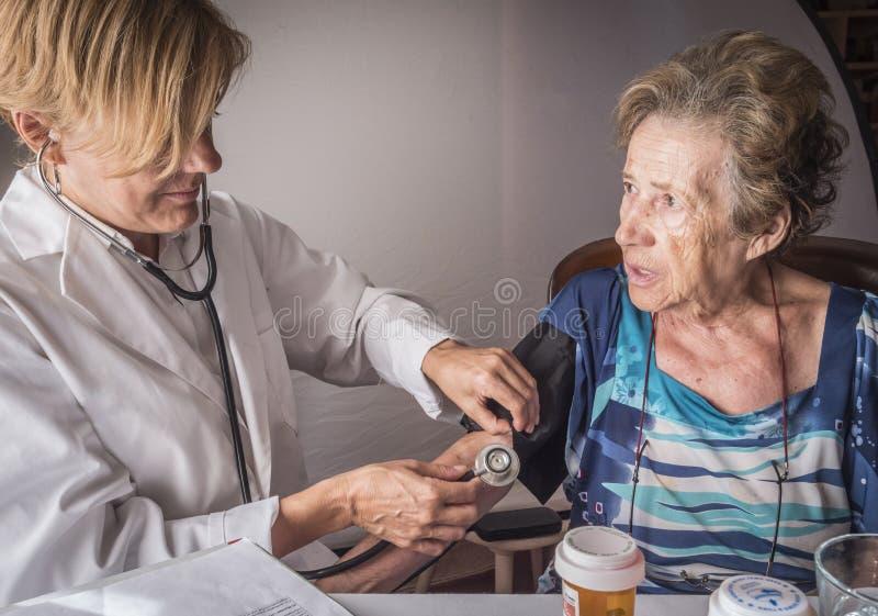 Soignez les mesures la tension artérielle au vieux à la maison image stock