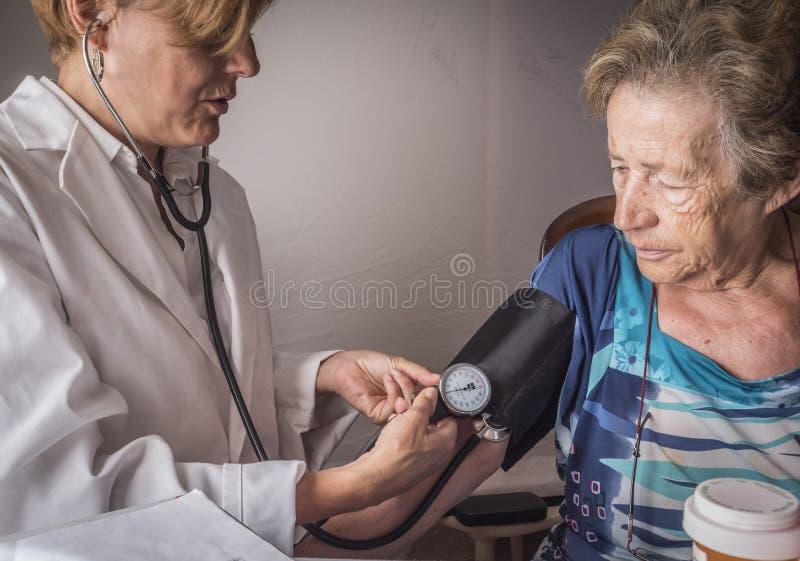 Soignez les mesures la tension artérielle au vieux à la maison photographie stock libre de droits