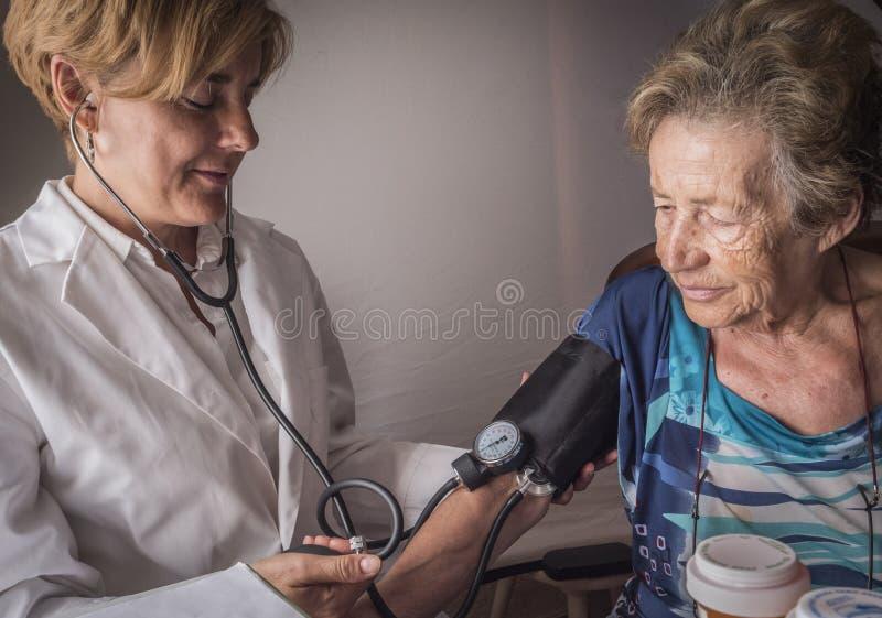 Soignez les mesures la tension artérielle au vieux à la maison photo libre de droits