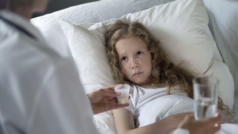 Soignez les pilules de offre ? l'enfant malheureux avec le bas syst?me immunitaire, ?pid?mie de grippe photo stock