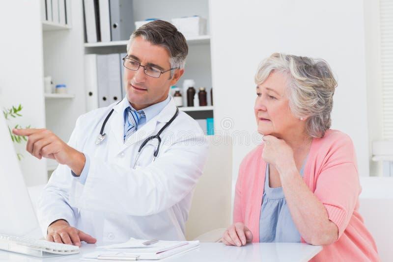 Soignez montrer des rapports au patient supérieur sur l'ordinateur photo stock