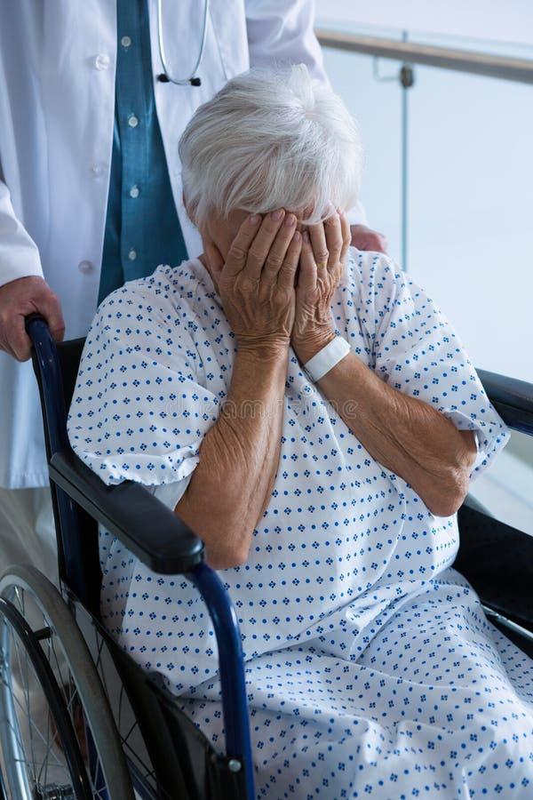 Soignez pousser le patient supérieur sur le fauteuil roulant dans le passage images stock