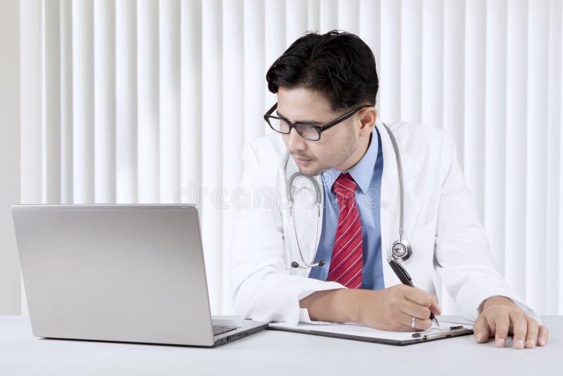 Soignez regarder son ordinateur portable tout en écrivant une prescription photos stock