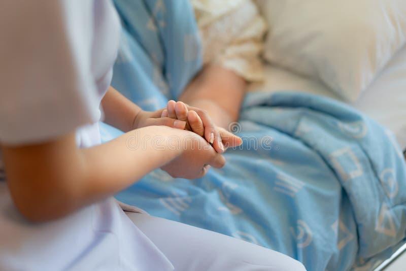 Soignez se reposer sur un lit d'h?pital ? c?t? des coups de main d'une femme plus ?g?e, concept de soin aux personnes ?g?es photos libres de droits