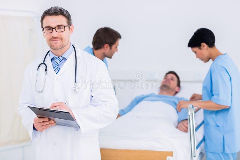 Soignez tenir des rapports avec le patient et le chirurgien à l'arrière-plan images libres de droits