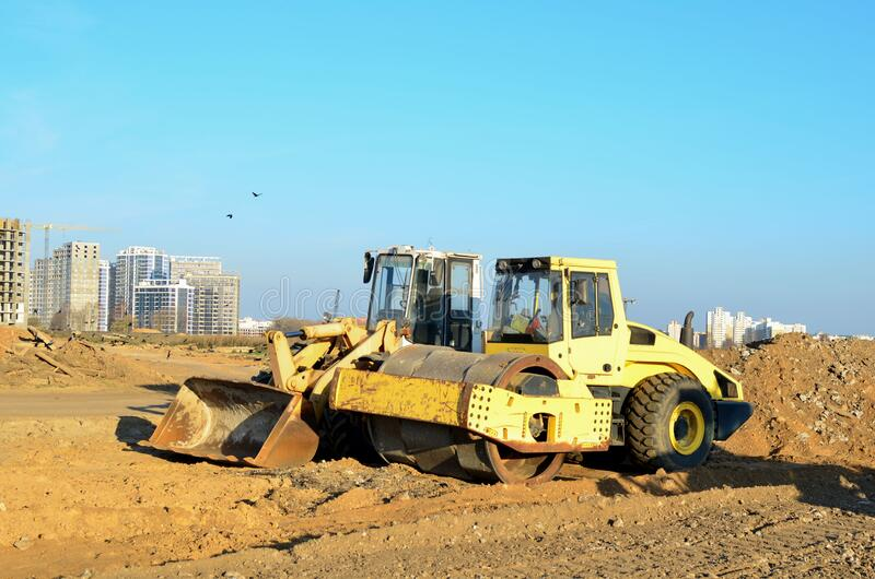 Soil Compactor and wheel loader at construction site. Vibration single-cylinder road roller leveling the ground for the construct. Of the foundation for royalty free stock images