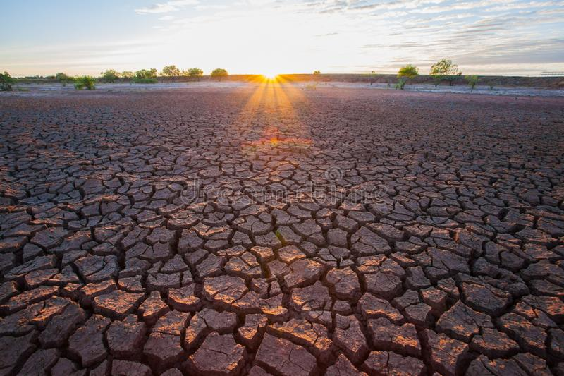 Soil crack on dry ground with sunset is shading background. Location at north east of Thailand royalty free stock image
