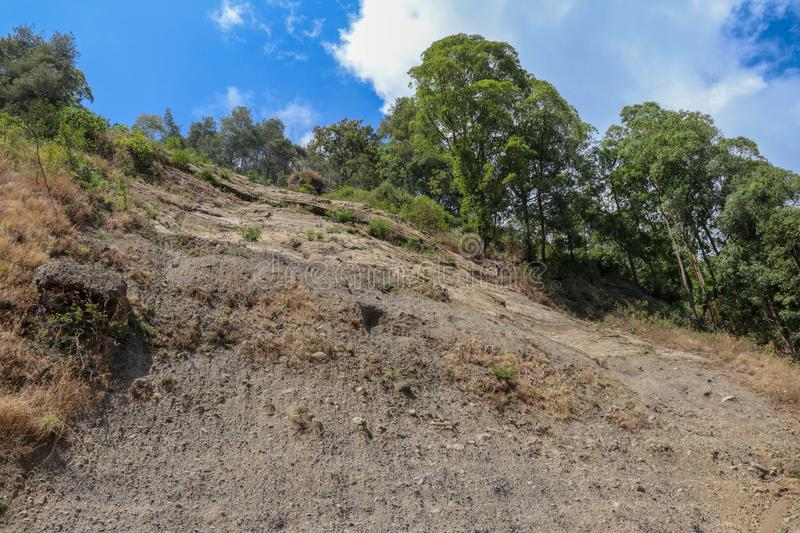 Soil erosion in the highlands. Landscape mountain with soil cracked. Rock outlier on background of mountains with forests, which a. Re greatly altered by erosion stock image
