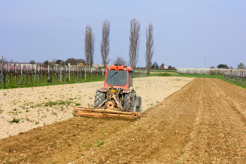 Soil preparation. Farmed land view - harrow for soil preparation - field with agricultural tractor preparing the ground for sowing stock photo