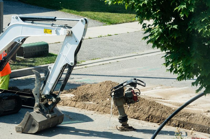 Soil compaction machine and excavator standing near the trench. Cable laying with optical fiber through a trench dug through an asphalt road royalty free stock photography