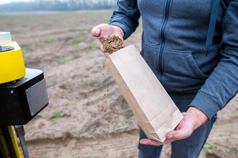 Soil Sampling. An engineer employee of a research laboratory packs a soil sample in a paper package. Automated probe for soil stock images
